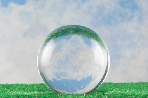 A crystal ball on grass before a blue sky
