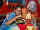 Close-up of a Latino boy with his grandmother eating dinner