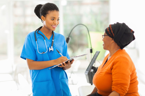 African medical nurse talking to a senior patient