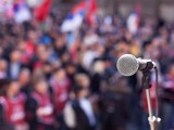 Image of a microphone in front of large crowd