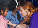 Einstein Global Health Fellowship participant examines child in Himalayas (India).