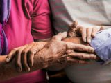 close up of elderly hands on each others forearms